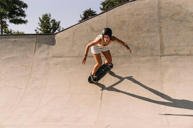 Fille moderne avec casque de patinage en demi-pipe