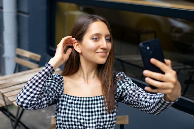Une fille moderne sourit et fait un portrait de selfie au téléphone tout en étant assise à la table dans un café en plein air