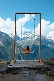 Une fille monte une balançoire dans les montagnes un paysage de prairies alpines de montagnes et de pics de glace
