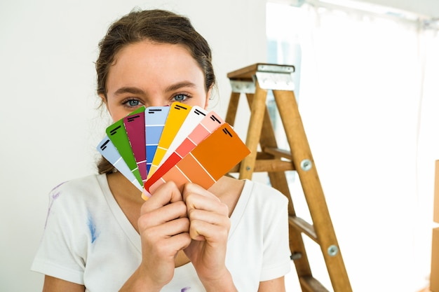 Fille montrant des échantillons de couleur à la caméra