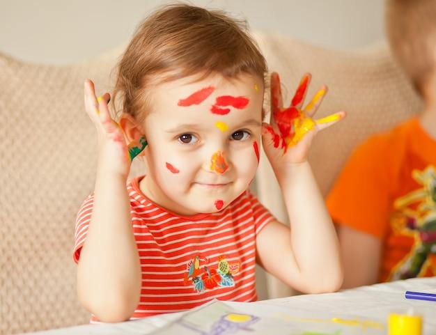 Fille montrant des mains peintes. mains peintes en peintures colorées. concept d'éducation, d'école, d'art et de peinture.
