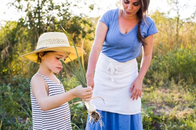 Fille montrant sa mère a récolté l'oignon de printemps dans le champ