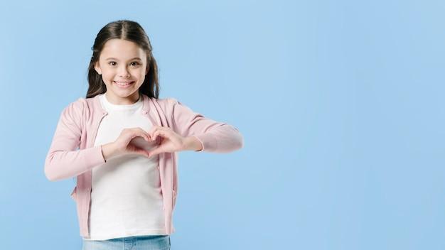 Fille montrant le signe du coeur en studio