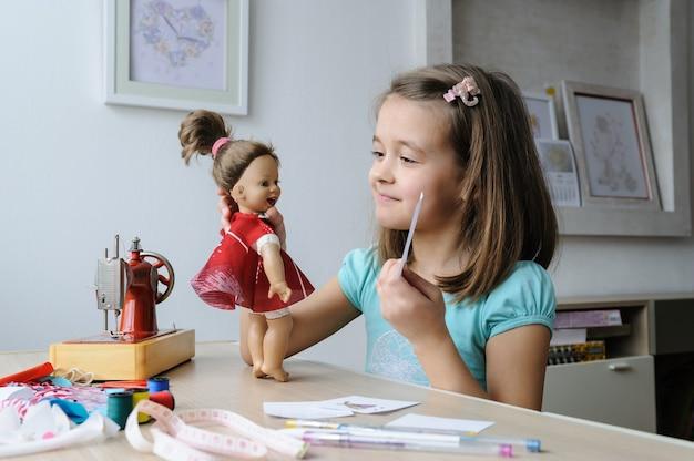 La fille montre à la poupée un croquis de la robe cousue.