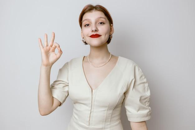 La fille montre le signe ok sur un fond clair