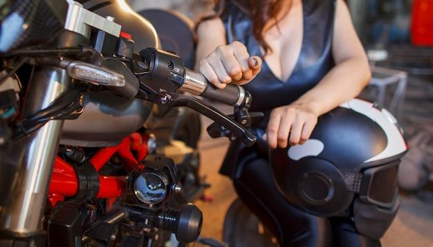 Fille de motard dans une robe en cuir au garage.