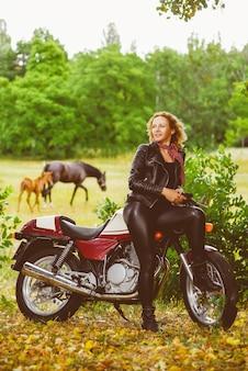 Fille de motard dans une veste en cuir sur une moto dans le contexte des chevaux.