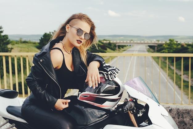 Fille de motard dans un vêtement en cuir sur une moto