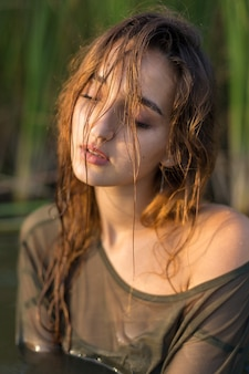 Fille mouillée dans l'eau avec des roseaux, portrait émotionnel d'une fille dans l'eau
