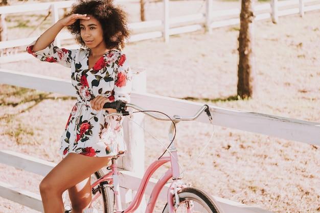 Une fille mulâtre se tient à côté de la piste de course avec vélo.