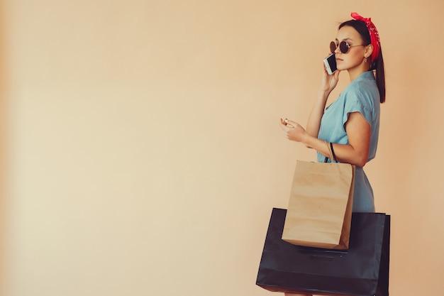 Fille sur un mur jaune avec des sacs à provisions