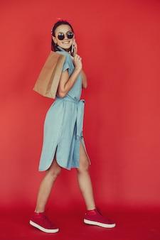 Fille sur un mur rouge avec des sacs à provisions