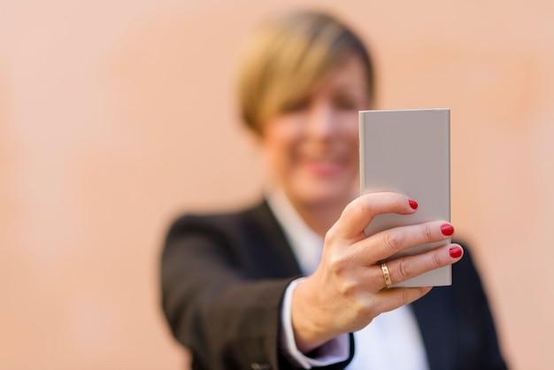 Fille mûre prenant un portrait de selfie avec son téléphone intelligent