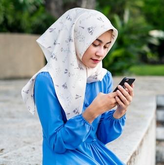Fille musulmane à l'aide d'un smartphone dans le parc