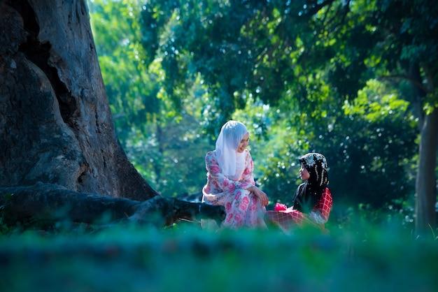 Fille musulmane asiatique avec une famille vivant et se relaxant sous un arbre en vacances. chez eux le matin, le soleil brille magnifiquement.