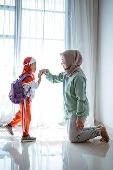Une fille musulmane serre la main et embrasse la mère avant d'aller à l'école