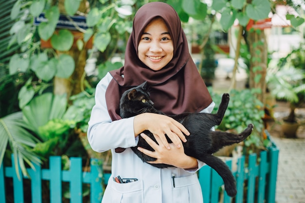 Une fille musulmane sourit avec son chat noir