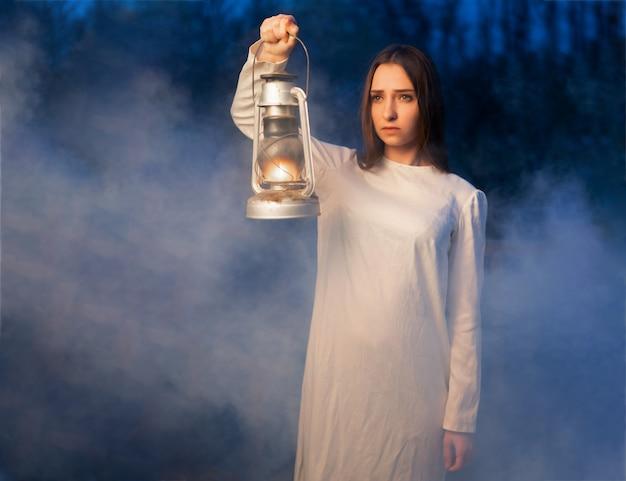 Fille mystique mystérieuse dans une forêt de nuit noire avec une lampe à pétrole dans ses mains