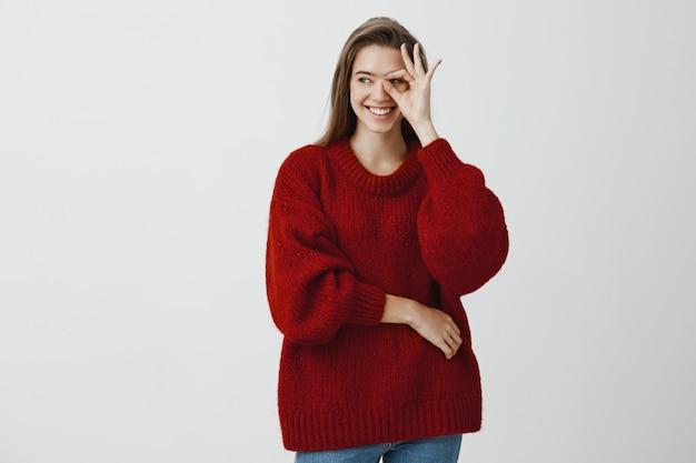La fille n'arrête jamais de s'occuper de son petit ami. femme caucasienne joyeuse confiante en pull rouge lâche, montrant bien ou grand signe sur les yeux et regardant de côté avec un sourire heureux