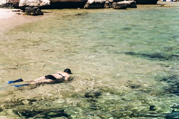 Fille nage avec un masque dans la mer