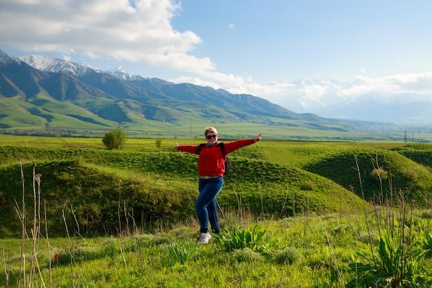 Fille sur la nature avec joie regarde les montagnes.