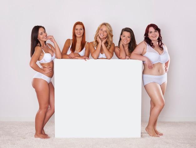 Fille naturelle en sous-vêtements posant avec tableau blanc vide