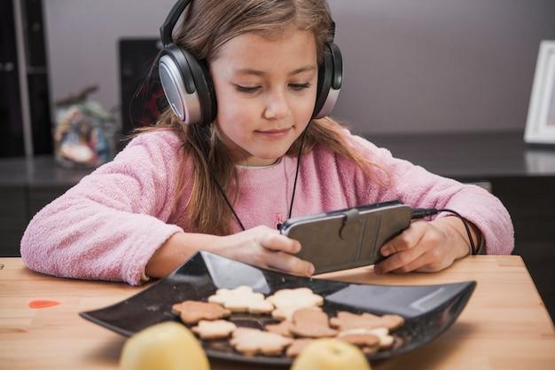 Fille, naviguer sur smartphone à table