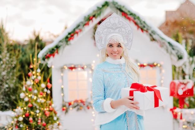 Fille des neiges avec un cadeau dans ses mains posant dans la neige