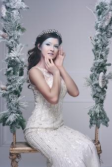 Fille des neiges avec couronne sur balançoire