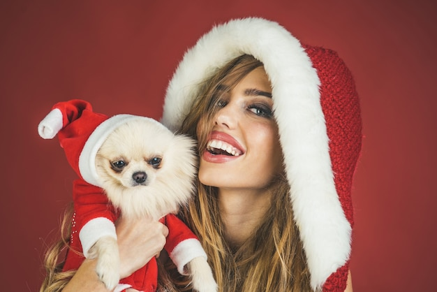 Fille de noël et animal de compagnie. femme avec petit chien en chapeau de père noël. concept de noël, nouvel an, hiver et personnes - femme souriante heureuse avec joli visage et petit chien. animal de compagnie, ami, concept d'amitié.