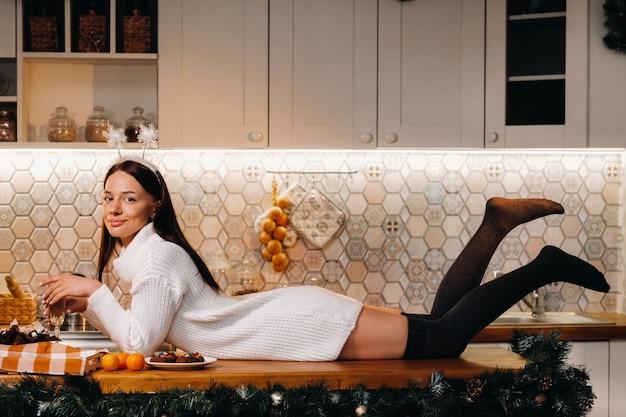 Une fille à noël est allongée sur la table de la cuisine et tient une coupe de champagne.femme le soir du nouvel an avec du champagne