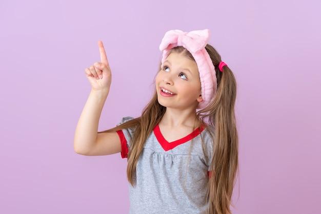 Une fille avec un nœud rose sur la tête pointe vers le haut.