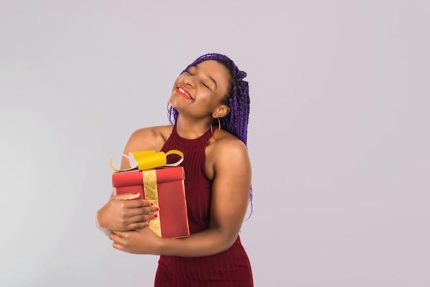 Une fille noire apprécie un gros cadeau de noël rouge. la fille sourit et reçoit un cadeau. isolé sur bleu