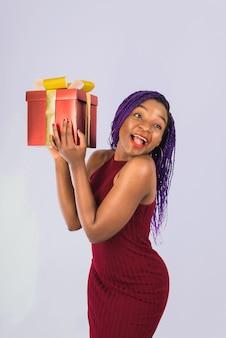 Une fille noire apprécie un gros cadeau de noël rouge. la fille sourit et reçoit un cadeau.