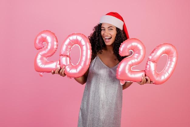Fille noire avec des ballons de vacances 2020 portant chapeau de noël isolé sur rose