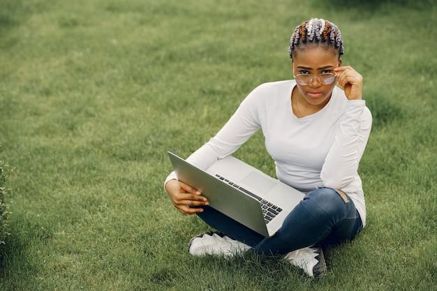Fille noire dans une ville d'été avec ordinateur portable