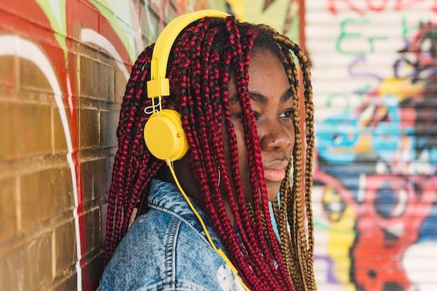 Fille noire exotique avec des tresses colorées dans ses cheveux et des écouteurs jaunes écoutant de la musique. appuyé sur un mur de graffitis.