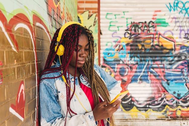 Fille noire exotique avec des tresses colorées dans ses cheveux et des écouteurs jaunes écoutant de la musique sur son téléphone portable. appuyé sur un mur de graffitis.