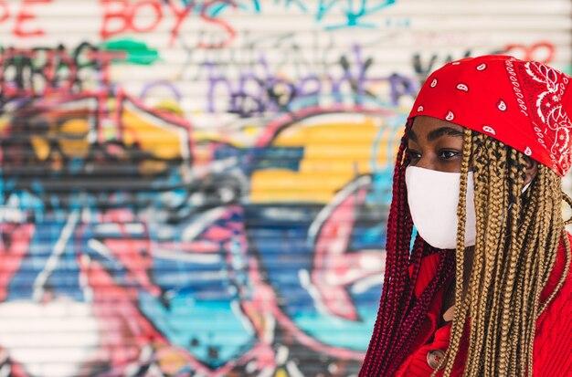 Fille noire exotique avec des tresses colorées et un masque facial. portant un foulard rouge sur la tête. appuyé sur un mur de graffitis.