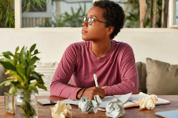 Une fille noire réfléchie en lunettes se concentre sur le côté, essaie de se rassembler avec des pensées