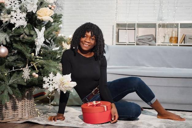 Une fille noire souriante aux cheveux bouclés est assise près d'un arbre de noël