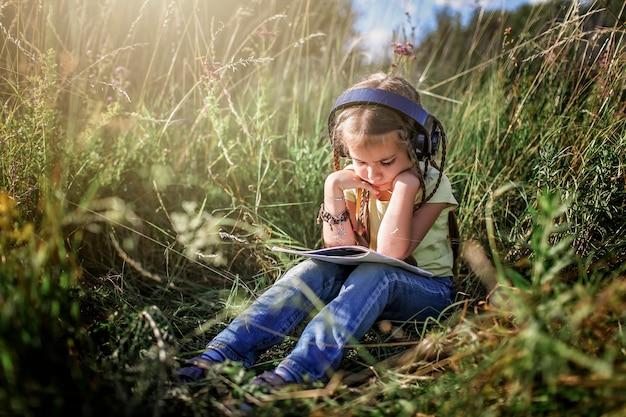 Fille avec de nombreuses tresses et écouteurs écouter de la musique et écrire du texte musical au champ de fleurs
