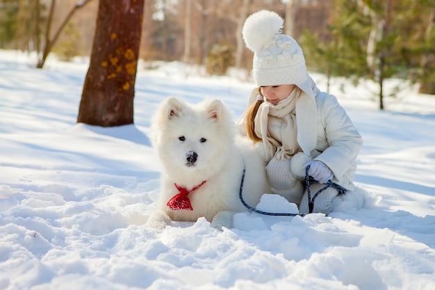 Une fille nourrit un chien de samoyède à poil ras en hiver, dehors dans la neige.