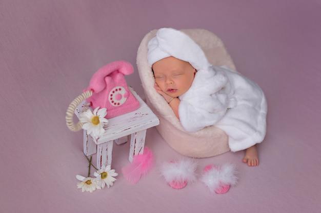Fille nouveau-née après les soins spa se trouve dans un fauteuil dans un peignoir et appelle sur un téléphone rose