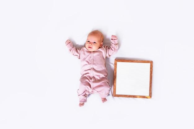 Fille nouveau-née sur blanc avec plaque de texte