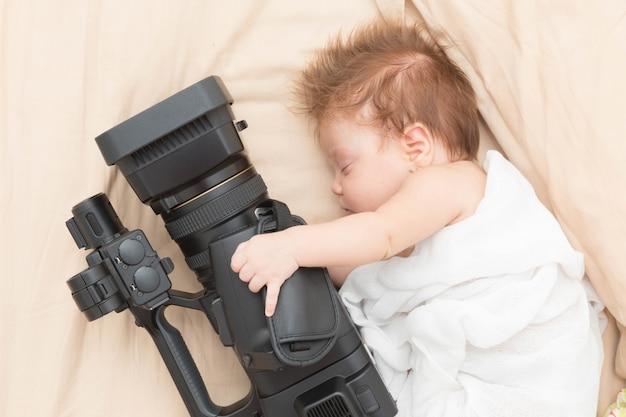 Fille nouveau-née endormie tenant une caméra vidéo.