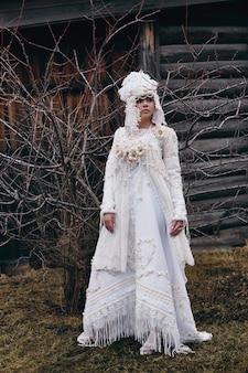 Fille nouvelle mode ethnique russe vogue vêtements créatifs posent près de la vieille maison, robe blanche et chapeau, vêtements ethniques, mode russe. déguisements, mystérieuse jeune fille.