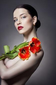 Fille nue nue avec des fleurs de tulipes dans le maquillage de la main