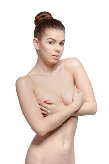 Fille nue qui vérifie soigneusement les mains ses seins
