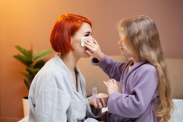 Fille oblige maman à se maquiller à la maison sur le lit